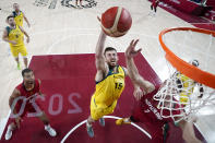 Australia's Nic Kay (15) scores over Team Germany's Johannes Voigtmann (7) during a men's basketball preliminary round game at the 2020 Summer Olympics, Saturday, July 31, 2021, in Saitama, Japan. (AP Photo/Eric Gay)