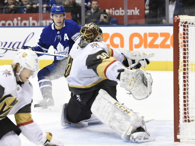 Toronto Maple Leafs center Mitchell Marner, back, watches as a goal by center John Tavares, goes in for an overtime goal past Vegas Golden Knights goaltender Malcolm Subban during an NHL hockey game Thursday, Nov. 7, 2019, in Toronto. (Nathan Denette/The Canadian Press via AP)
