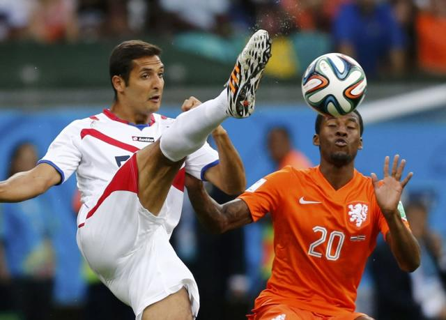 Costa Rica's Celso Borges (L) fights for the ball against Georginio Wijnaldum of the Netherlands during their 2014 World Cup quarter-finals at the Fonte Nova arena in Salvador July 5, 2014. REUTERS/Marcos Brindicci (BRAZIL - Tags: SOCCER SPORT WORLD CUP)