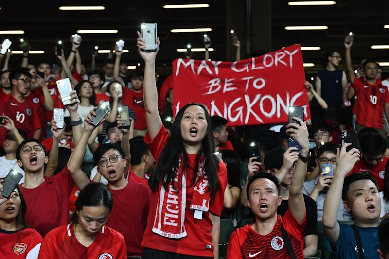 HONG KONG, CHINA - SEPTEMBER 10: Football fans hold up their phones and shout during a protest at the end of the World Cup qualifying match between Hong Kong and Iran at Hong Kong Stadium on September 10, 2019 in Hong Kong, China. Pro-democracy protesters have continued demonstrations across Hong Kong despite the withdrawal of a controversial extradition bill as demonstrators call for the city's Chief Executive Carrie Lam to immediately meet the rest of their demands, including an independent inquiry into police brutality, the retraction of the word 'riot' to describe the rallies, and the right for Hong Kong people to vote for their own leaders. (Photo by Carl Court/Getty Images)