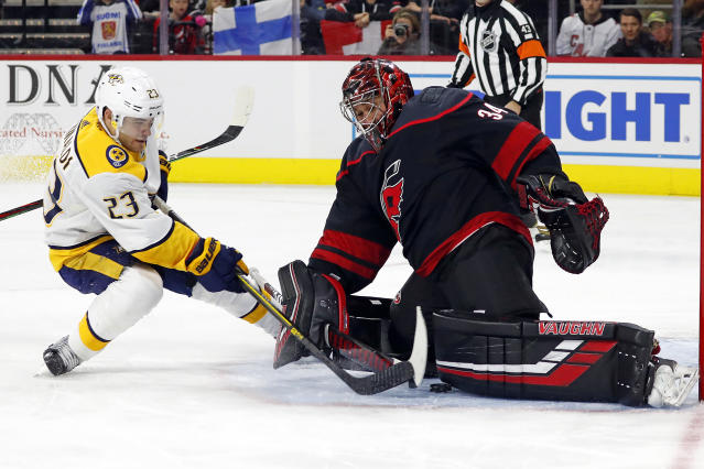 Nashville Predators' Rocco Grimaldi (23) slips the puck between the legs of Carolina Hurricanes goaltender Petr Mrazek (34), of the Czech Republic, for a goal during the first period of an NHL hockey game in Raleigh, N.C., Friday, Nov. 29, 2019. (AP Photo/Karl B DeBlaker)