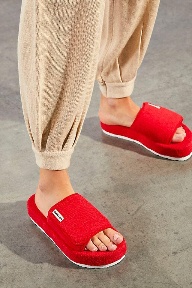 """<h2>Hunter Terry Slide Sandals</h2><br>Ring the alarm! These fire-engine red terrycloth slides are touchable enough to keep on while padding around the house — and will happily announce their stylish presence once you've hit the sidewalks, too.<br><br><strong>Hunter</strong> Terry Beach Slide Sandals, $, available at <a href=""""https://go.skimresources.com/?id=30283X879131&url=https%3A%2F%2Fwww.freepeople.com%2Fshop%2Fhunter-terry-beach-slide-sandals%2F%3Fcategory%3Dshoes%26color%3D060%26type%3DREGULAR%26quantity%3D1"""" rel=""""nofollow noopener"""" target=""""_blank"""" data-ylk=""""slk:Free People"""" class=""""link rapid-noclick-resp"""">Free People</a>"""
