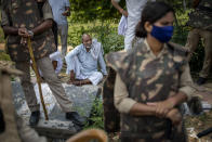 An elderly Indian farmer sits in the shade as others block a highway during a protest in Noida, India, Friday, Sept. 25, 2020. Hundreds of Indian farmers took to the streets on Friday protesting new laws that the government says will boost growth in the farming sector through private investments, but they fear these are likely to be exploited by private players for buying their crops cheaply. (AP Photo/Altaf Qadri)