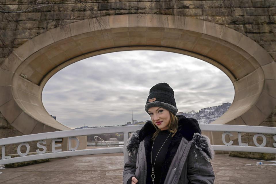 "In this Monday, Feb. 8, 2021, photo, Allissa Star poses for a photograph along the north shore of the Allegheny River in Pittsburgh. Starr worked about a week every month at a brothel in Pahrump, Nev., outside of Las Vegas. Then the pandemic led to the shuttering of Nevada's licensed bordellos, the only place where prostitution is legal in the state, and they have remained closed since March, leaving sex workers like Starr struggling to pay the bills and turning to alternatives like ""virtual"" dates. (AP Photo/Keith Srakocic)"