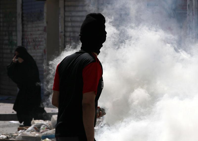 Bahraini anti-government protesters react to tear gas fired by riot police during clashes in Daih, Bahrain, on Thursday, Feb. 14, 2013, the second anniversary of the start of a pro-democracy uprising in the Gulf island kingdom. Protests began at daybreak in opposition areas nationwide as protesters attempted to return to the well-barricaded main site of the uprising. (AP Photo/Hasan Jamali)