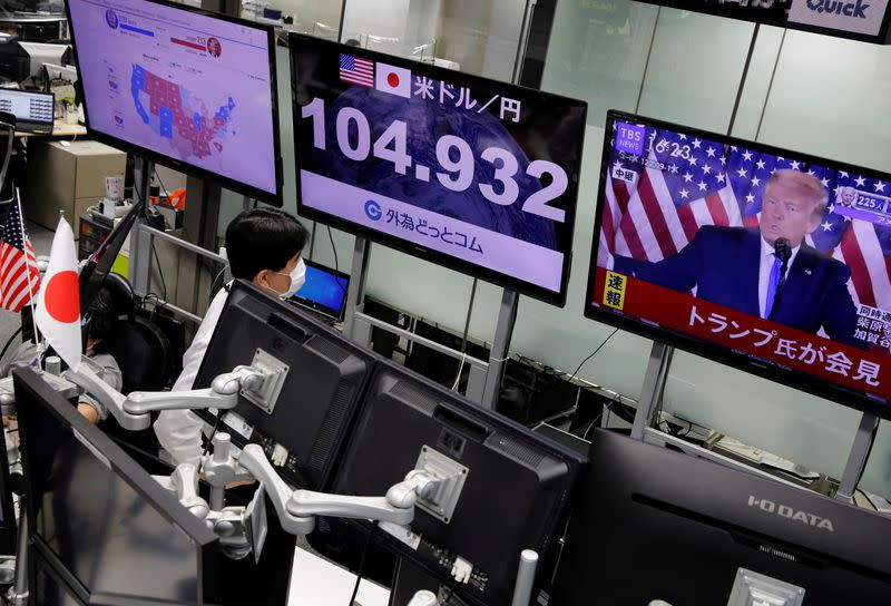 An employee of the foreign exchange trading company Gaitame.com watches a TV broadcast of U.S. President Donald Trump's speech at a dealing room in Tokyo
