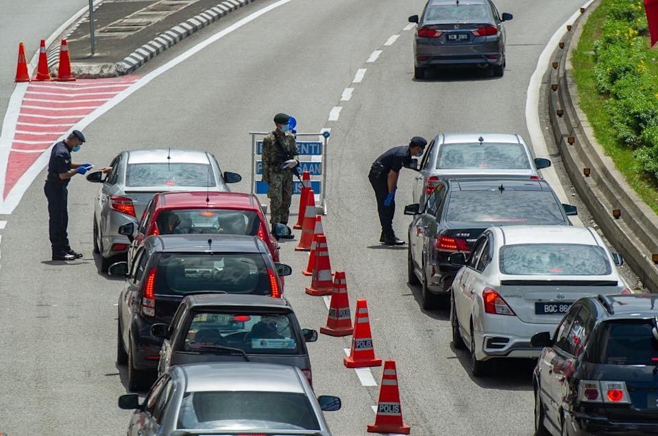 Police officers conducting checks at a roadblock in Jalan Kuching, Kuala Lumpur January 31, 2021. PH's Economic Committee first said the government must put a stop to the implementation of repeated lockdowns and subsequent confusion triggered by ever-changing standard operating procedures (SOPs). — Picture by Shafwan Zaidon