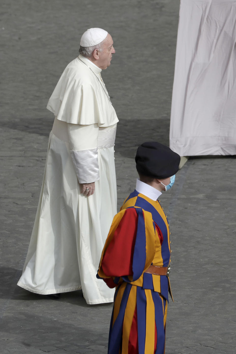 FILE - In this Sept. 2, 2020 file photo, Pope Francis walks by a Vatican Swiss guard wearing a face mask to prevent the spread of COVID-19 as he arrives at the San Damaso courtyard for his general audience, the first with faithful since February when the coronavirus outbreak broke out, at the Vatican. On Monday, Oct. 12, 2020, the Vatican said in a statement that four Swiss Guards have tested positive for the coronavirus, as the surge in infections in surrounding Italy enters the Vatican walls. (AP Photo/Andrew Medichini, file)