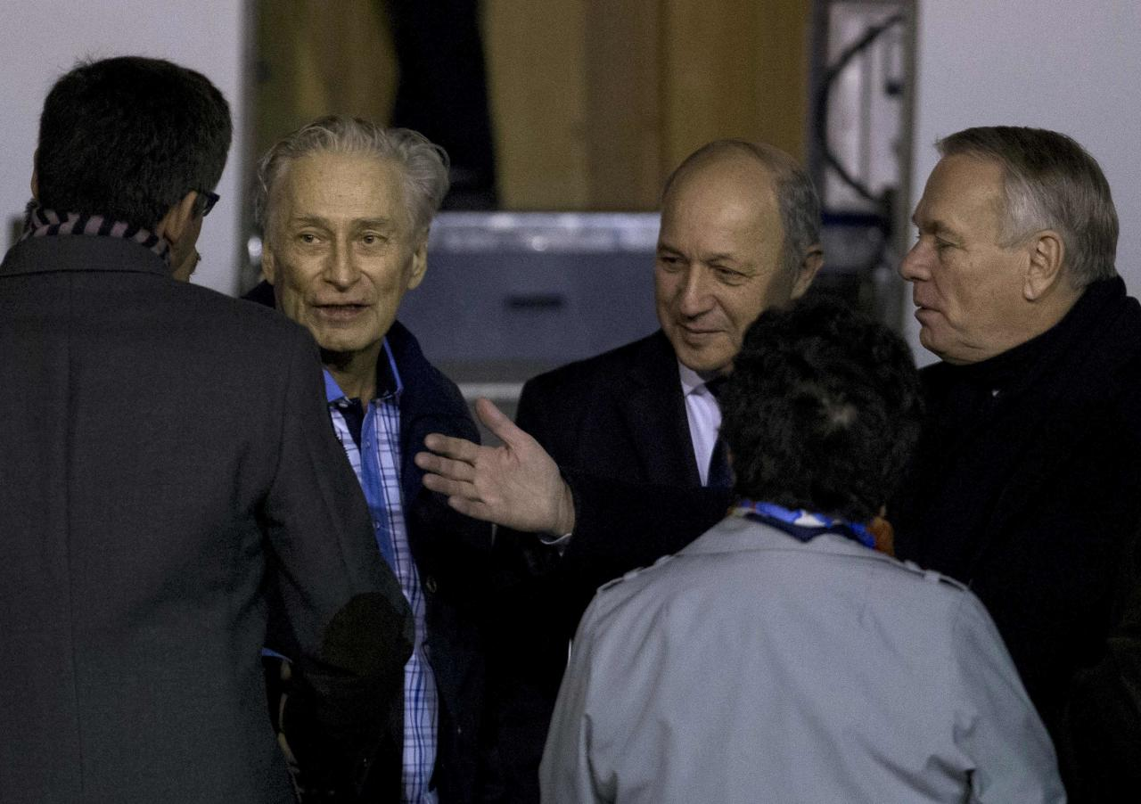 Former French hostage Francis Collomp (2ndL) is welcomed by relatives and officials including Prime Minister Jean-Marc Ayrault (R) and Foreign Affairs minister Laurent Fabius on the tarmac upon his arrival at Villacoublay military airport, near Paris, November 18, 2013. Collomp, a French engineer who had been held hostage by Islamist militants in northern Nigeria for almost a year, has escaped his jailers, France's president said on Sunday. REUTERS/Kenzo Tribouillard/Pool (FRANCE - Tags: POLITICS)