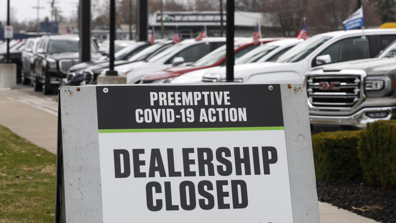 A sign showing an automobile dealership closed as a preemptive COVID-19 action, Thursday, March 26, 2020 jn Detroit. Automakers' moves to reopen plants in the U.S. come as new auto sales are expected to fall dramatically for the month of March. Edmunds.com expects March sales to fall nearly 36% from a year earlier. (AP Photo/Paul Sancya)