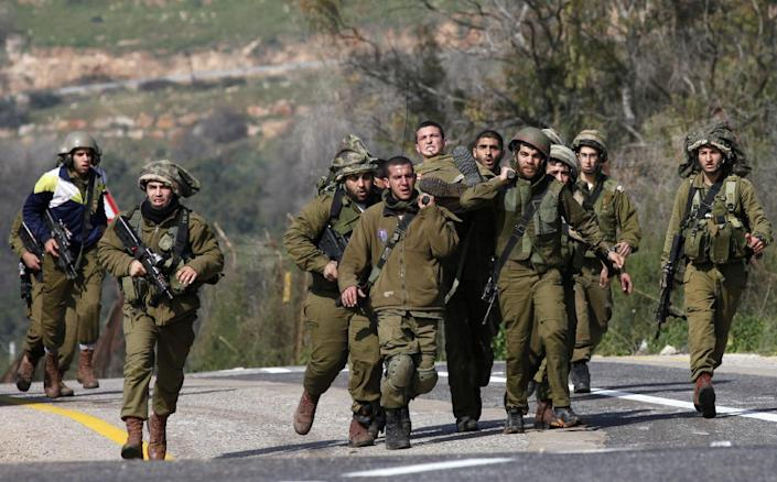 Israeli soldiers carry an injured comrade after an anti-tank missile hit an army vehicle in an occupied area on the border with Lebanon, on January 28, 2015 (AFP Photo/Jalaa Marey)