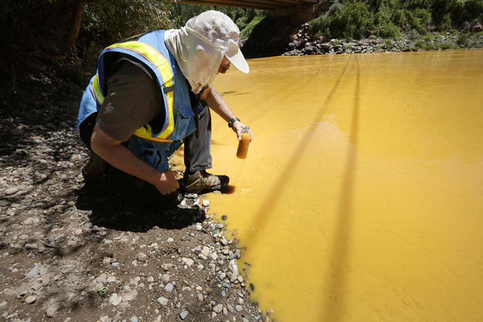 FILE - In this Aug. 6, 2015, file photo, Dan Bender of the La Plata County Sheriff's Office takes a water sample from the Animas River near Durango, Colo., after the accidental release of an estimated 3 million gallons of waste from the Gold King Mine. The Navajo Nation's Department of Justice announced on Wednesday, Jan. 13, 2021, has settled with two mining companies to resolve claims stemming from a 2015 spill that sent wastewater downstream from the inactive Gold King Mine in southwestern Colorado. (Jerry McBride/The Durango Herald via AP, File)