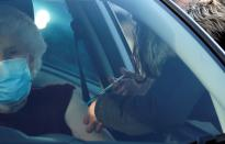 A woman receives the Pfizer-BioNTech COVID-19 vaccine at a drive through vaccination centre amid the outbreak of the coronavirus disease (COVID-19) in Hyde, Britain