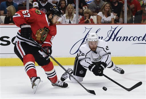 Los Angeles Kings center Trevor Lewis (22) dives for the puck against Chicago Blackhawks center Michael Frolik (67) during the second period of Game 1 of the NHL hockey Stanley Cup Western Conference finals, Saturday, June 1, in Chicago. (AP Photo/Nam Y. Huh)