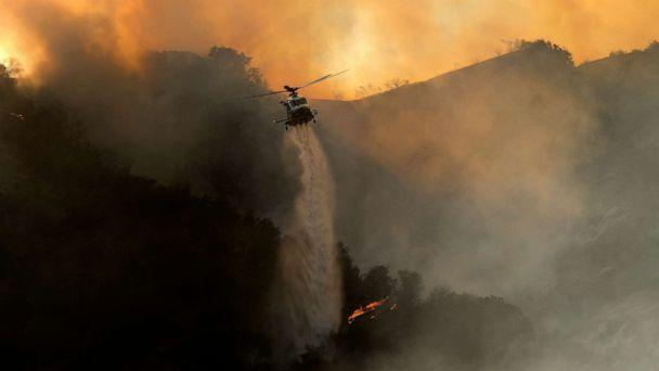 PHOTO: A firefighting helicopter drops water onto a brush fire scorching in the Pacific Palisades area of Los Angeles, May 15, 2021. (Ringo H.w. Chiu/AP)