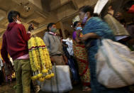 A flower vendor stands with a bunch of garlands for sale as shoppers walk past at a wholesale flower market ahead of the Hindu festival of Dussehra, in Bengaluru, India, Friday, Oct. 23, 2020. Weeks after India fully opened up from a harsh lockdown and began to modestly turn a corner by cutting new infections by near half, a Hindu festival season is raising fears that the disease could spoil the hard-won gains. Health experts worry the festivals can set off a whole new cascade of infections, further testing and straining India's battered health care system. (AP Photo/Aijaz Rahi)