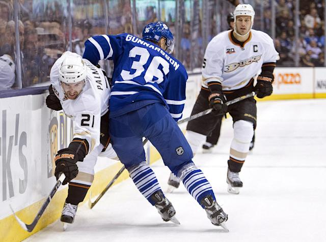 Toronto Maple Leafs defenseman Carl Gunnarsson (36) hip checks Anaheim Ducks forward Kyle Palmieri (21) into the boards as Ducks forward Ryan Getzlaf, right, look on during the first period of an NHL hockey game in Toronto on Tuesday, Oct. 22, 2013. (AP Photo/The Canadian Press, Nathan Denette)