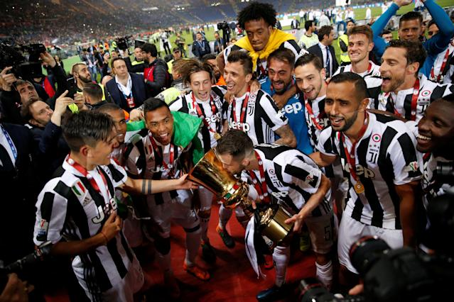 Soccer Football - Coppa Italia Final - Juventus vs AC Milan - Stadio Olimpico, Rome, Italy - May 9, 2018 Juventus' Miralem Pjanic kisses the trophy surrounded by team mates as they celebrate after winning the Coppa Italia REUTERS/Stefano Rellandini