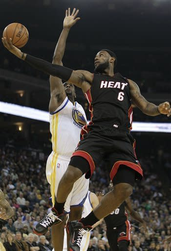 Miami Heat's LeBron James (6) lays up a shot over Golden State Warriors' Ekpe Udoh (20) during the first half of an NBA basketball game, Tuesday, Jan. 10, 2012, in Oakland, Calif. (AP Photo/Ben Margot)