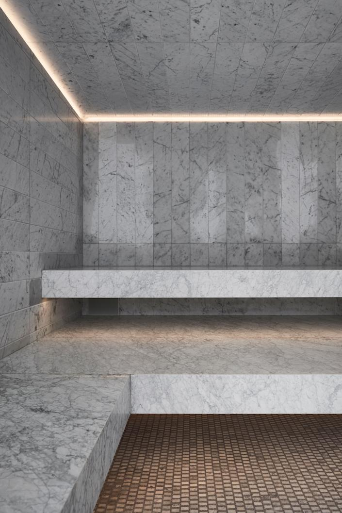 "<div class=""caption""> Carrara marble walls and Carrara terrazzo floors in the steam room. </div>"
