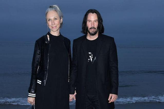 Alexandra Grant and Keanu Reeves arrive for the Saint Laurent runway show in Malibu, Calif., on June 6. (Photo: Valerie MACON/AFP via Getty Images)