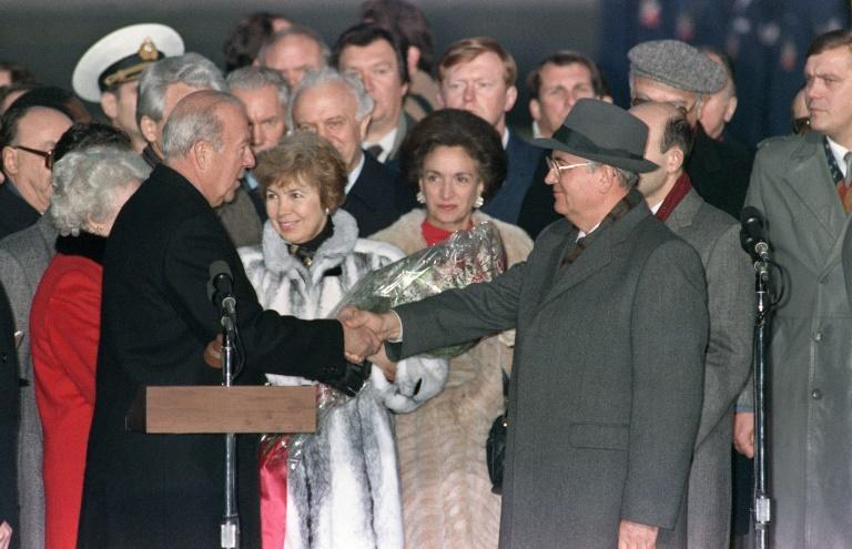 Soviet leader Mikhail Gorbachev (R) and his wife Raisa are greeted by US Secretary of State George Shultz upon their arrival in the United States on December 7, 1987