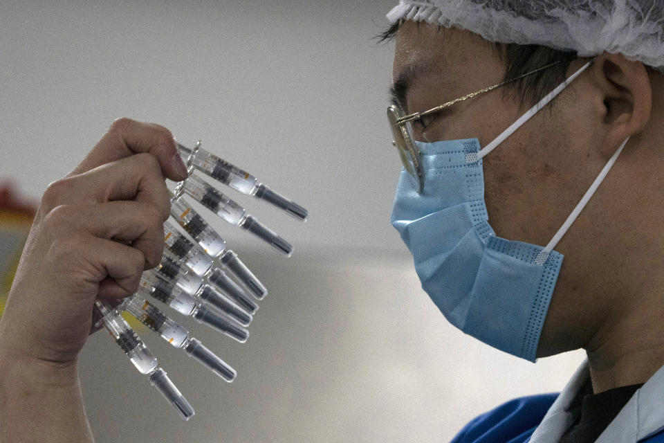 FILE - In this Sept. 24, 2020, file photo, a worker inspects syringes of a vaccine for COVID-19 produced by Sinovac at its factory in Beijing. China approved two new more COVID-19 vaccines for wider use Thursday, adding to its growing arsenal of shots: one from CanSino Biologics, and a second one from state-owned Sinopharm. (AP Photo/Ng Han Guan, File)