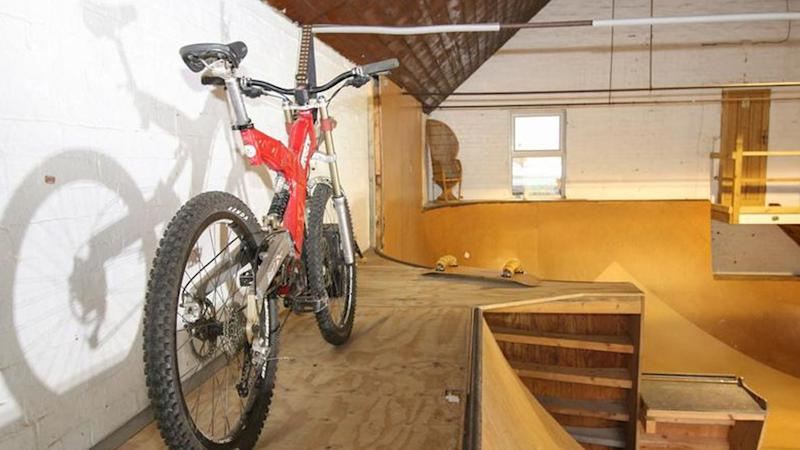 A bike is parked in the indoor skate park.