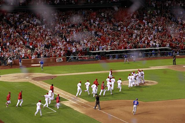 Members of the St. Louis Cardinals run onto the field to celebrate after their 7-0 win over the Chicago Cubs in a baseball game to clinch the National League Central title Friday, Sept. 27, 2013, in St. Louis. (AP Photo/Jeff Roberson)