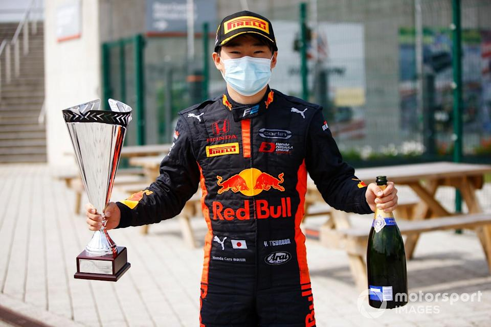 """Yuki Tsunoda, Carlin poses with his winner's trophy and champagne<span class=""""copyright"""">Andy Hone / Motorsport Images</span>"""