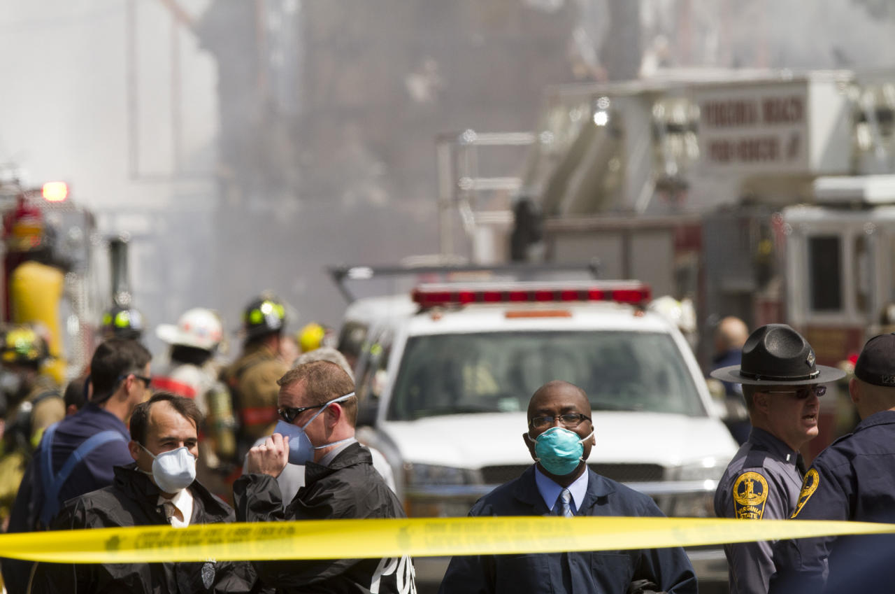 Virginia Beach police officers wear protective masks at the scene of a jet crash Friday, April 6, 2012 in Virginia Beach, Va. Two Navy pilots ejected from a fighter jet Friday, sending the unmanned plane careening into a Virginia Beach apartment complex and tearing the roof off at least one building that was engulfed in flames, officials said. Six people, including both pilots, were taken to hospitals, officials said. The Navy said both aviators on board the jet ejected before it crashed around noon and were being taken to hospitals for observation. (AP Photo/Virginian-Pilot, Bill Tiernan
