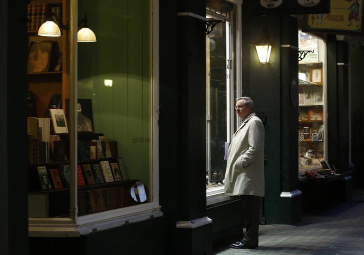 A man looks into the window of a shop in London