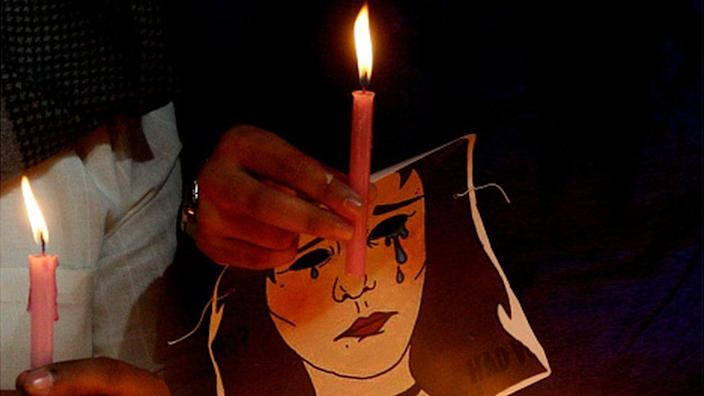 A woman holds a candle at an anti-rape protest in Delhi