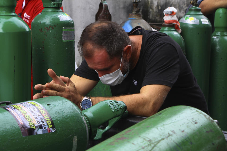 A family member of a patient hospitalized with COVID-19 waits in line in hopes of refilling empty oxygen tanks, outside the Nitron da Amazonia company, in Manaus, Amazonas state, Brazil, Friday, Jan. 15, 2021. (AP Photo/Edmar Barros)