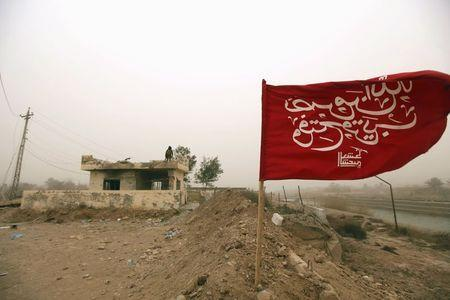 A Shi'ite militia flag bearing a verse from the Koran is seen on the outskirts of Diyala province, north of Baghdad February 8, 2015. REUTERS/Ahmed Saad