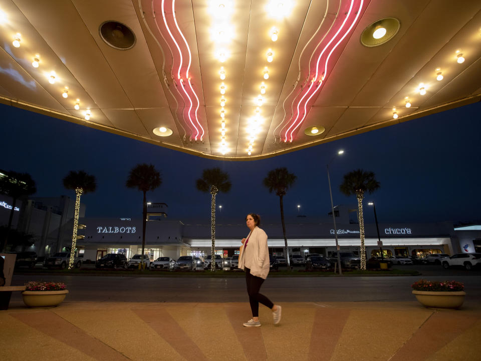 "A woman walks past by River Oaks Theatre's neon marquee on the second last day of the theater Wednesday, March 24, 2021, in Houston. The historic theater that director Richard Linklater called his ""film school"" and that for decades was the place to catch hard-to-find independent and foreign films has closed for good. Like many U.S. movie theaters and other businesses, the River Oaks Theatre was a victim of the coronavirus pandemic.(Yi-Chin Lee/Houston Chronicle via AP)"