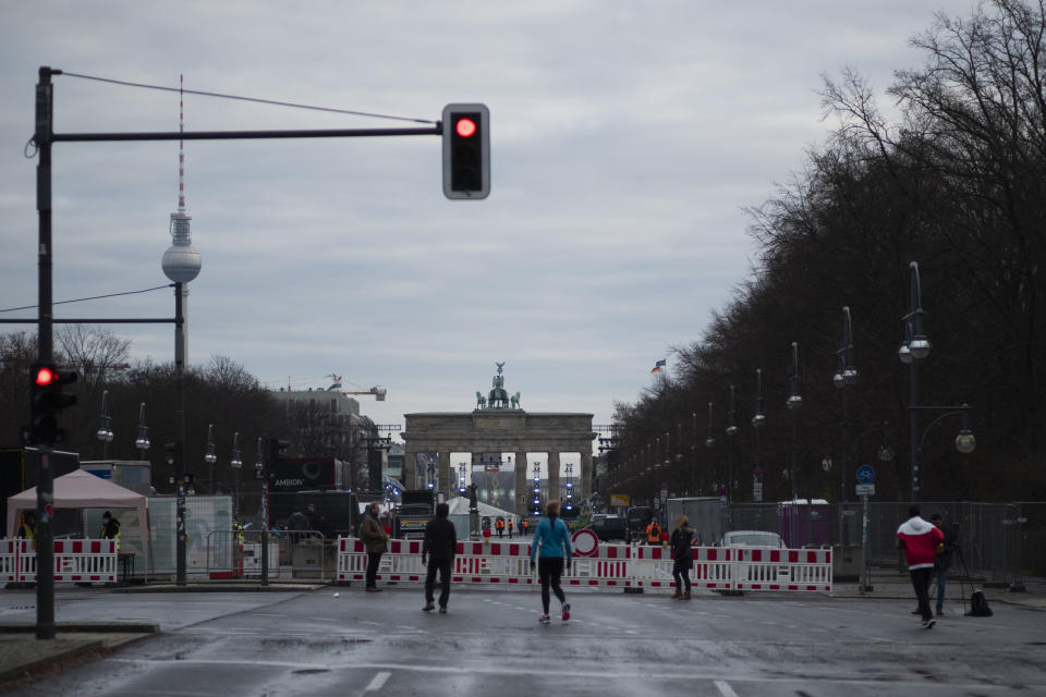 People stand on the blocked boulevard 'Strasse des 17. Juni' on New Year's Eve in Berlin, Germany, Thursday, Dec. 31, 2020. The boulevard is the main place for New Year's celebration in the German capital but because of the COVID-19 pandemic the road is closed and all public celebrations are banned. (AP Photo/Markus Schreiber)