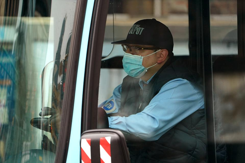 A bus driver wears a mask following the outbreak of coronavirus disease (COVID-19), in the Manhattan borough of New York City, New York, U.S., March 20, 2020. REUTERS/Carlo Allegri