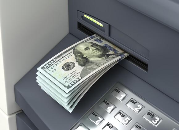 A stack of $100 bills coming out of an ATM.