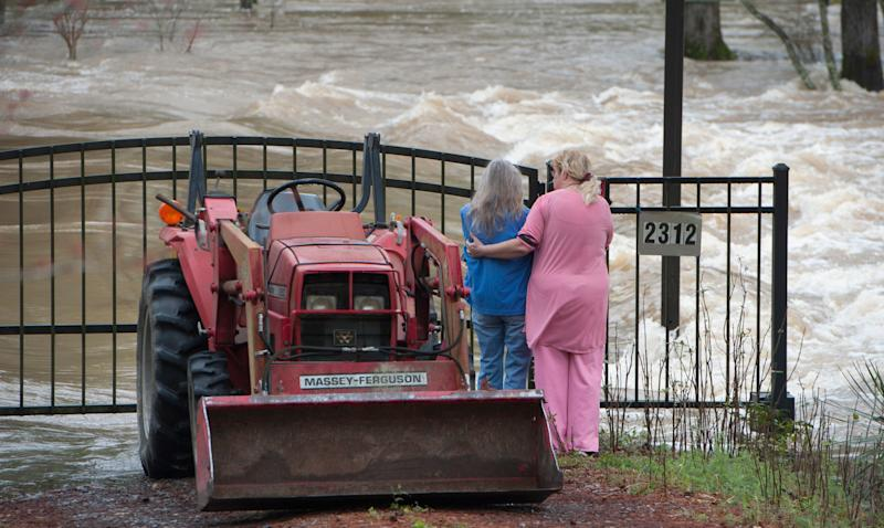Kathy Covington, center, watches the powerful floodwaters of the Pearl River rush through her Florence, Miss., yard on Feb. 16, 2020.