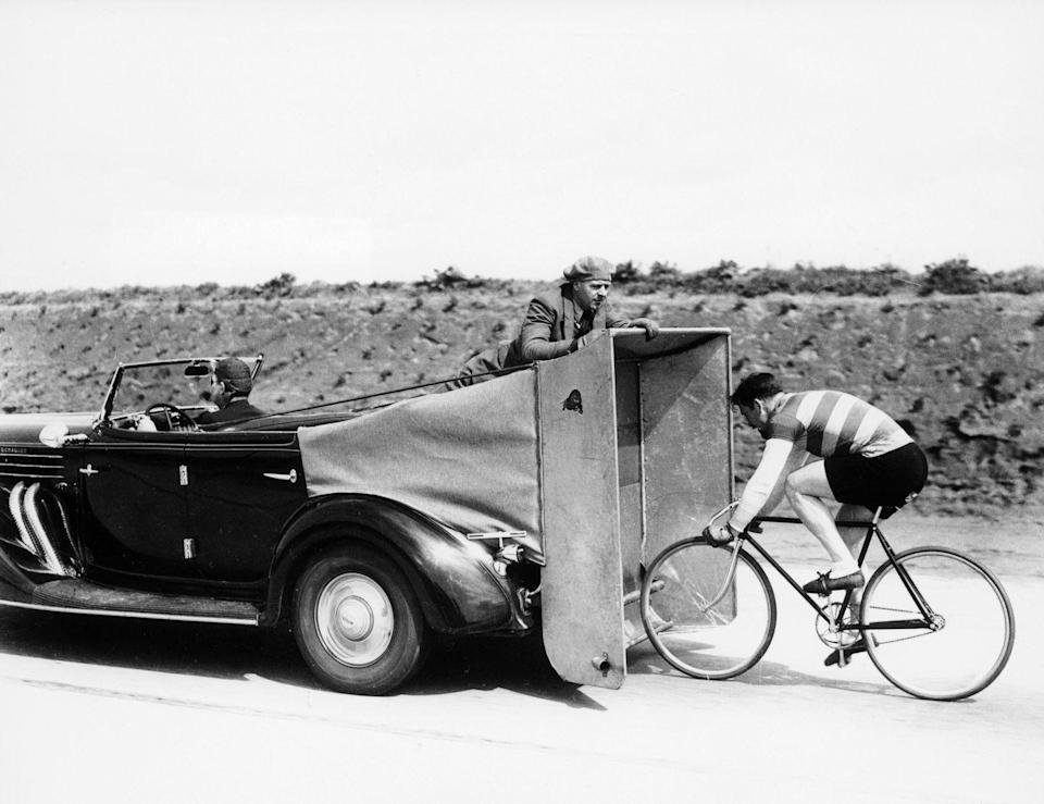 <p>In this photo snapped in 1935, the cyclist appears to be hard at work, pedaling behind a car towing an improvised windbreaker. </p>