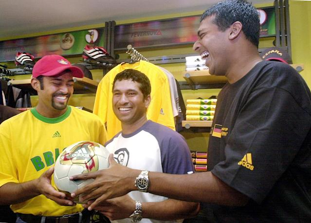 """BANGALORE, INDIA: Tennis players Leander Paes (L) and Mahesh Bhupati (R) share a joke with ace Indian cricketer Sachin Tendulkar (C) at a function in Bangalore 17 December 2001 to launch the official match ball for the 2002 Soccer World Cup, """"Fevernova"""". The three sportsmen are the Indian brand ambassadors for adidas, the official sponsor of the 2002 World Cup. It has become common among Indian sportspersons to endorse commercial products to supplement their income. AFP PHOTO/INDRANIL MUKHERJEE (Photo credit should read INDRANIL MUKHERJEE/AFP/Getty Images)"""