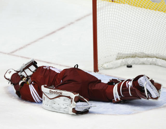 Phoenix Coyotes goalie Mike Smith (41) lies on the ice after getting hit in the second period during an NHL hockey game against the Detroit Red Wings on Saturday, Oct. 19, 2013, in Glendale, Ariz. The goal was disallowed after a review. (AP Photo/Rick Scuteri)