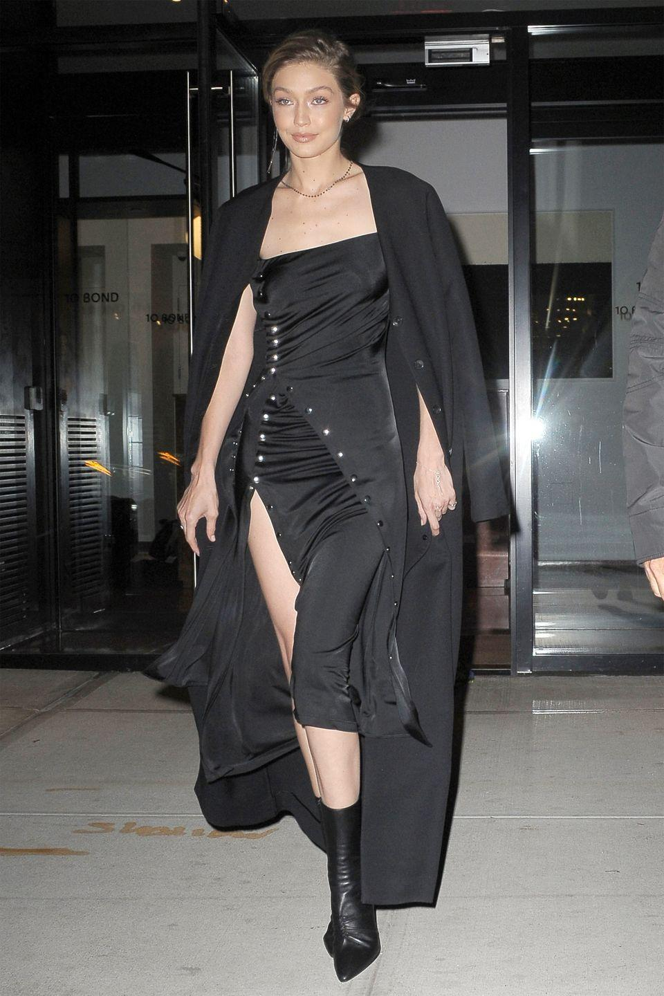 <p>In a layered black silk dress, draped coat, and black leather sock boots while leaving her apartment in NYC for the Aperture Gala.</p>