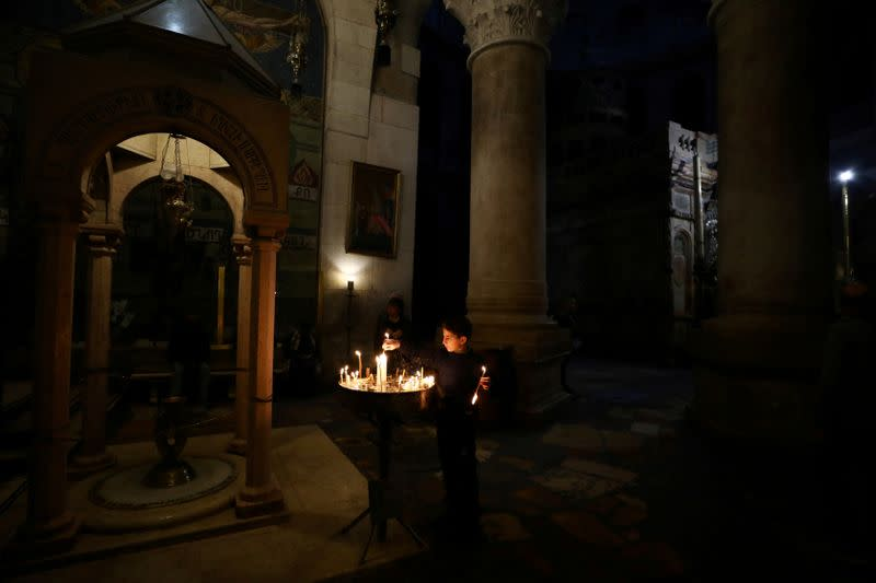 FILE PHOTO: A boy lights candles in the Church of the Holy Sepulchre in Jerusalem's Old City