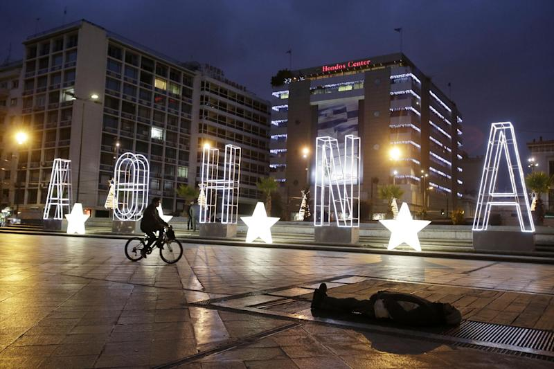 A man rides his bicycle next to a lit Christmas sign reading ''Athens'' as a homeless man sleeps on a metro air vent above an underground station to warm up, at Omonia Square in central Athens, Monday, Dec. 16, 2013. Homelessness has increased dramatically during the financial crisis in Greece, which has depended on international rescue loans for more than three years. Drastic spending cuts imposed through six years of recession have led to massive job losses, with the September unemployment rate reaching 27.4 percent. (AP Photo/Thanassis Stavrakis)