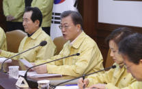 """South Korean President Moon Jae-in, center, speaks during a meeting at a government complex in downtown Seoul, South Korea, Sunday, Feb. 23, 2020. South Korea's president has put the country on its highest alert for infectious diseases and says officials should take """"unprecedented, powerful"""" steps to fight a viral outbreak. (Lee Jin-wook/Yonhap via AP)"""