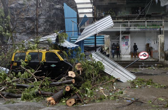 A taxi car that was damaged after a tree fell on it during a heavy rain in Mumbai, India, Monday, May 17, 2021. Cyclone Tauktae, roaring in the Arabian Sea was moving toward India's western coast on Monday as authorities tried to evacuate hundreds of thousands of people and suspended COVID-19 vaccinations in one state. (AP Photo/Rajanish Kakade)