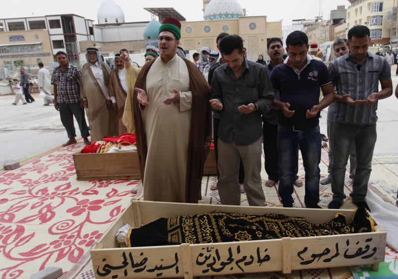 Mourners pray over the two bodies killed in a car bomb attack before their burial in the holy Shiite city of Najaf, 160 kilometers (100 miles) south of Baghdad, Iraq, Monday, May 20, 2013. A wave of car bombings across Baghdad's Shiite neighborhoods and in the southern city of Basra killed and wounded dozens of people, police said. (AP Photo/ Alaa al-Marjani)