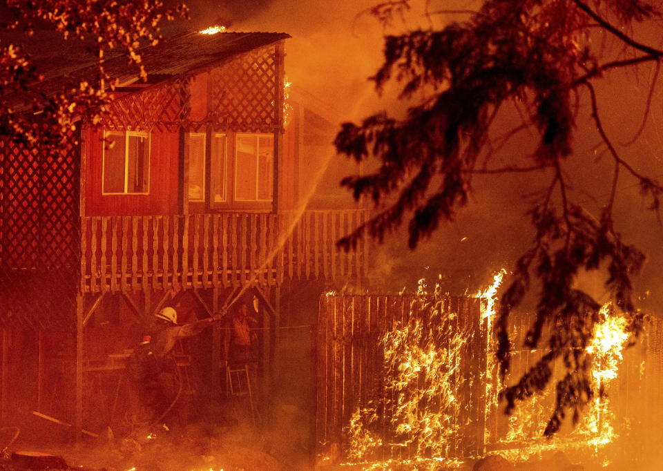 Firefighters work to save a home as the Dixie Fire tears through the Indian Falls community in Plumas County, Calif., on Saturday, July 24, 2021. The home, along with neighboring residences, ended up burning. (AP Photo/Noah Berger)